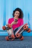 Patinador de sexo femenino joven que usa el teléfono móvil Foto de archivo libre de regalías