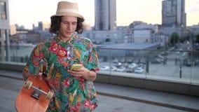 Patinador de sexo masculino que usa el teléfono mientras que camina con el tablero metrajes