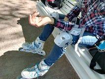 Patinador del rodillo de la muchacha con el equipo de seguridad - cojines de la rodilla y de codo fotos de archivo libres de regalías