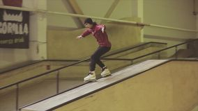 Patinador del rodillo en diapositiva de la camisa de tela escocesa en el trampolín Manía extrema Competencia en skatepark metrajes