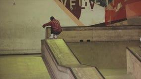 Patinador del rodillo en el salto en el trampolín, tirón, diapositiva de la camisa Manía extrema Competencia en skatepark almacen de metraje de vídeo