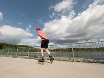 Patinador del rodillo en la acción El paseo del hombre en patines en línea monta a lo largo de la barandilla de la 'promenade', c Fotografía de archivo libre de regalías