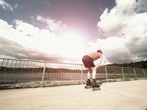 Patinador del rodillo en la acción El paseo del hombre en patines en línea monta a lo largo de la barandilla de la 'promenade', c Imagenes de archivo