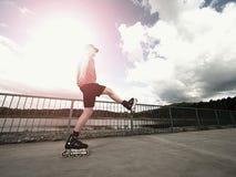 Patinador del rodillo en la acción El paseo del hombre en patines en línea monta a lo largo de la barandilla de la 'promenade', c Fotografía de archivo