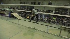 Patinador del rodillo en paseo del sombrero en la cerca salto Manía extrema Competencia en skatepark audiencias metrajes
