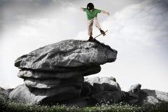 Patinador en equilibrio en la roca Fotografía de archivo
