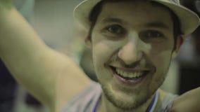 Patinador feliz del rodillo en sombrero con la medalla en cuello en etapa en la competencia en skatepark Ganador almacen de video
