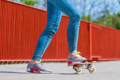 Patinador humano de las piernas con el monopatín en la calle Fotos de archivo