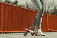 Patinador humano de las piernas con el monopatín en la calle Imagenes de archivo