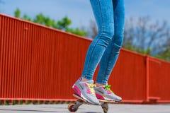 Patinador humano de las piernas con el monopatín en la calle Foto de archivo