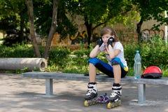 Patinador joven del rodillo que toma un resto Fotos de archivo