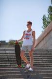 Patinador joven en un fondo azul Adolescente con un monopatín que camina abajo de las escaleras Concepto adolescente de la moda C Imagen de archivo