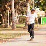 Patinador joven que rueda abajo la calle Foto de archivo