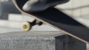 Patinador que hace boardslide del frente del truco de la diapositiva en el banco de la calle, a cámara lenta almacen de video