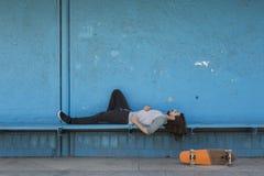 Patinador que miente en fondo azul con un monopatín anaranjado cerca de él fotografía de archivo libre de regalías