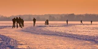 Patinadores de hielo en el lago congelado Imágenes de archivo libres de regalías