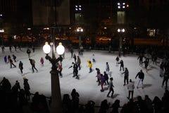 Patinadores de hielo en la pista de hielo de la tribuna de McCormick, parque del milenio, avenida de Michigan, Chicago imagenes de archivo