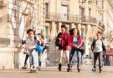 Patinadores en línea y skateres que montan en ciudad Fotografía de archivo