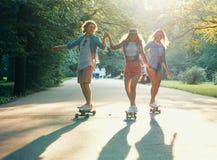Patinadores felices jovenes al aire libre Foto de archivo libre de regalías