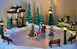 Patinadores miniatura del invierno con el fondo blanco imagen de archivo