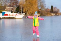 Patinage de glace d'enfant sur le canal congelé de moulin en Hollande image libre de droits