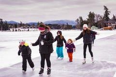 Patinage de glace de filles sur le lac mirror image stock