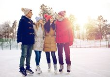 Patinage de glace heureux d'amis sur la piste dehors Photo libre de droits