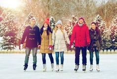 Patinage de glace heureux d'amis sur la piste dehors Image stock
