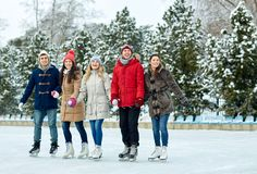 Patinage de glace heureux d'amis sur la piste dehors Images stock