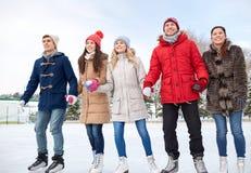 Patinage de glace heureux d'amis sur la piste dehors Photos libres de droits