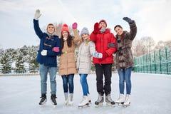 Patinage de glace heureux d'amis sur la piste dehors Photographie stock