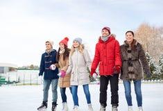Patinage de glace heureux d'amis sur la piste dehors Image libre de droits