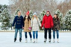Patinage de glace heureux d'amis sur la piste dehors Photos stock