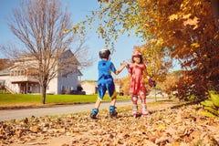 Patinage de rouleau heureux de petits enfants et donner cinq Image stock