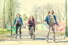 Patinage de rouleau de l'adolescence de filles et monte d'une bicyclette au parc Photos stock