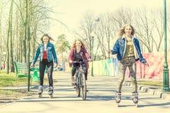 Patinagem de rolo adolescente das meninas e montada de uma bicicleta no parque Fotos de Stock