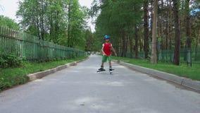 Patinagem de rolo nova do menino na estrada video estoque