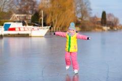 Patinagem no gelo da criança no canal congelado do moinho na Holanda imagem de stock royalty free