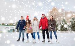 Patinagem no gelo feliz dos amigos na pista fora fotografia de stock