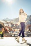 Patinaje de hielo bonito de la muchacha al aire libre en la pista de hielo Fotografía de archivo