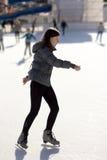 Patinaje de hielo de la mujer joven en una pista de hielo Imagen de archivo libre de regalías
