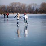 Patinaje de hielo de los pares al aire libre en una charca Fotografía de archivo