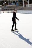 Patinaje de hielo delgado de la mujer joven en una pista de hielo Fotos de archivo libres de regalías