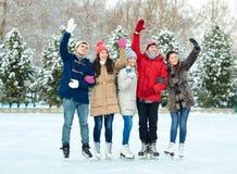 Patinaje de hielo feliz de los amigos en pista al aire libre Foto de archivo libre de regalías