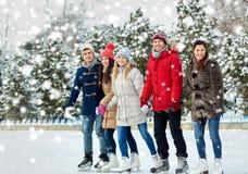 Patinaje de hielo feliz de los amigos en pista al aire libre Imágenes de archivo libres de regalías