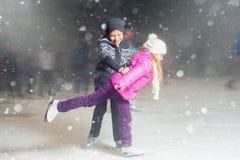 Patinaje de hielo feliz de los niños en la pista de hielo, noche del invierno Imagen de archivo libre de regalías