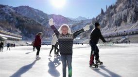 Patinaje de hielo feliz de la muchacha en la pista al aire libre en el invierno almacen de metraje de vídeo
