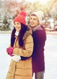 Patinaje de hielo feliz de los pares en pista al aire libre Fotografía de archivo libre de regalías
