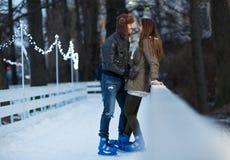 Patinaje de hielo feliz de los pares, de la muchacha y del muchacho al aire libre en la pista Imagen de archivo