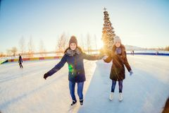 Patinaje de hielo hermoso de dos muchachas al aire libre en un día de invierno caliente Foto de archivo